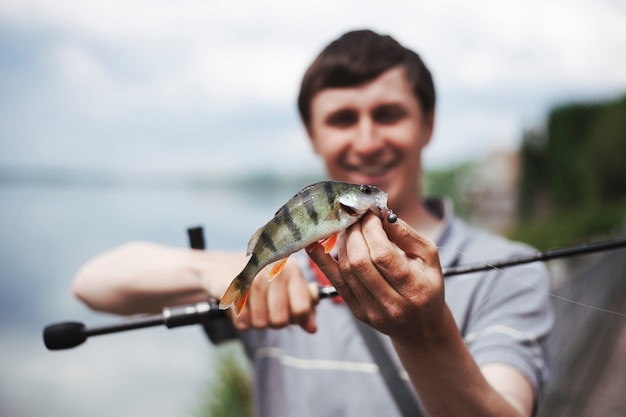 Portrait of man holding caught fish in the hook Free Photo