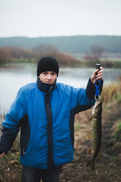 Portrait of a man holding pike fish looking at camera Free Photo