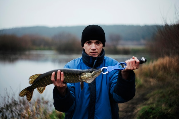 Portrait of a man holding pike fish Free Photo