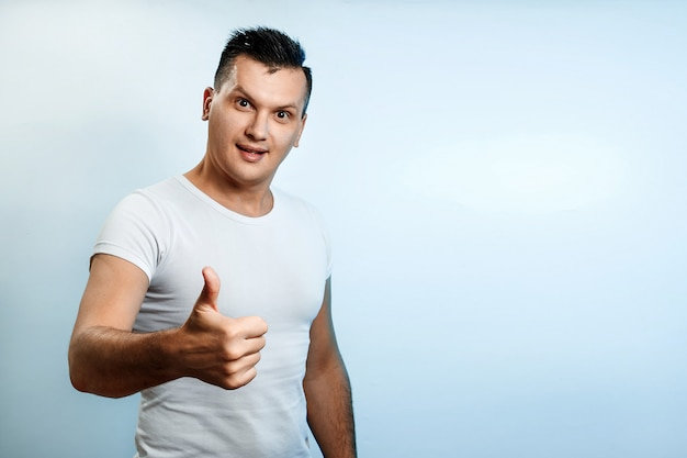 Portrait of a man on a light background, shows a thumbs up, puts a like. Premium Photo