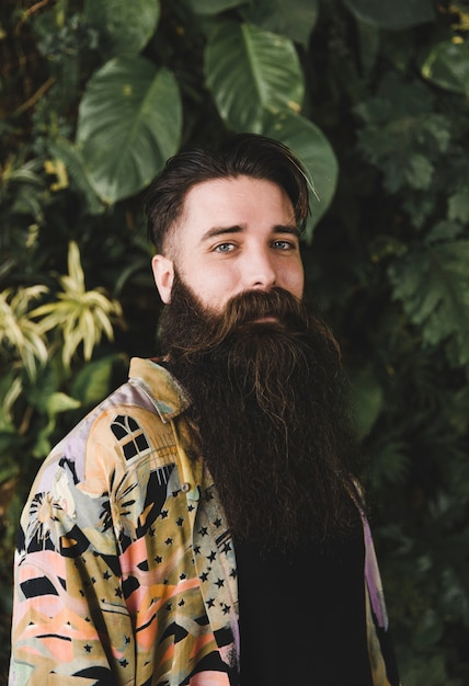 Portrait of a man looking at camera in front of plants Free Photo
