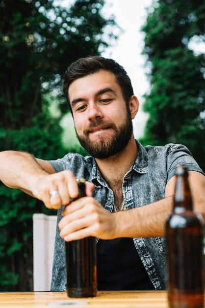 Portrait of a man opening the beer bottle cap Free Photo