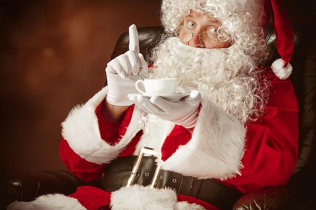 Ritratto di uomo in costume di babbo natale con una lussuosa barba bianca, cappello di babbo natale e un costume rosso al rosso seduto su una sedia con una tazza di caffè Foto Gratuite