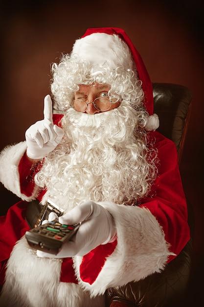 Ritratto di uomo in costume di babbo natale con una lussuosa barba bianca, cappello di babbo natale e un costume rosso al rosso seduto su una sedia con telecomando tv Foto Gratuite