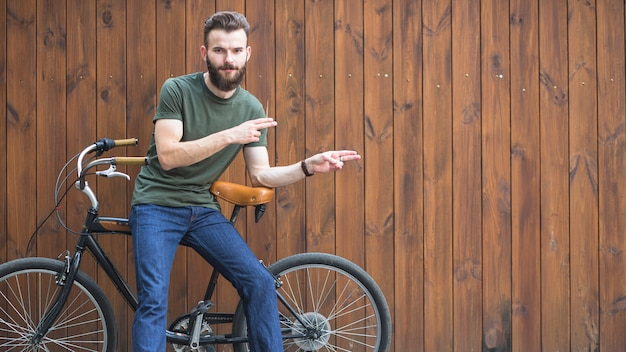Portrait of a man sitting on bicycle making hand gesture Free Photo