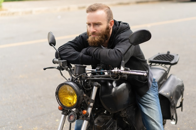 Portrait of man sitting on motorbike with pensive expression Free Photo