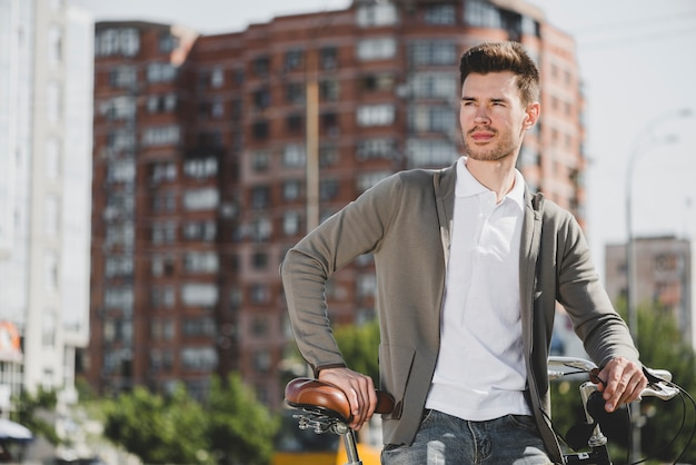 Portrait of man standing with bicycle in the city Free Photo