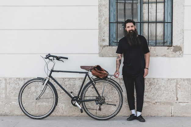 Portrait of a man standing with bicycle leaning on wall Free Photo