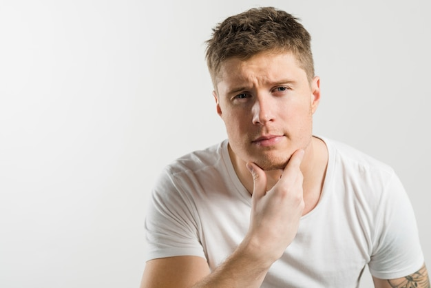 Portrait of a man strokes his chin after shaving against white backdrop Free Photo