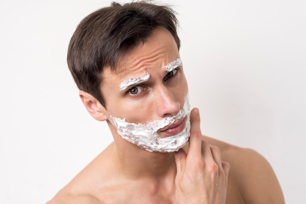 Portrait of a man thinking with shaving foam on face Free Photo