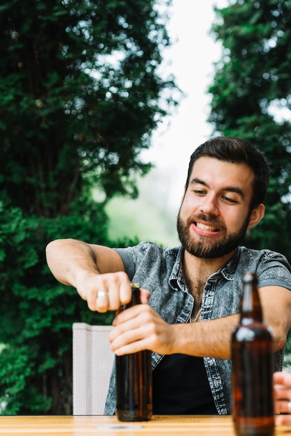 Portrait of a man trying to open the beer bottle cap Free Photo