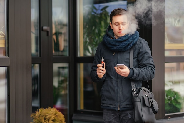 Portrait of man vaping a vaporizer outdoors. safe smoking. Free Photo