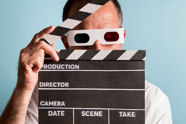 Portrait of a man wearing 3d glasses holding clapperboard in front of his face against blue backdrop Free Photo