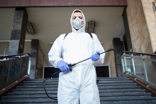 Portrait of man in white protection suit with sprayer tank ready for a fight against corona virus Free Photo