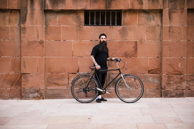 Portrait of a man with bicycle standing in front of red wall Free Photo