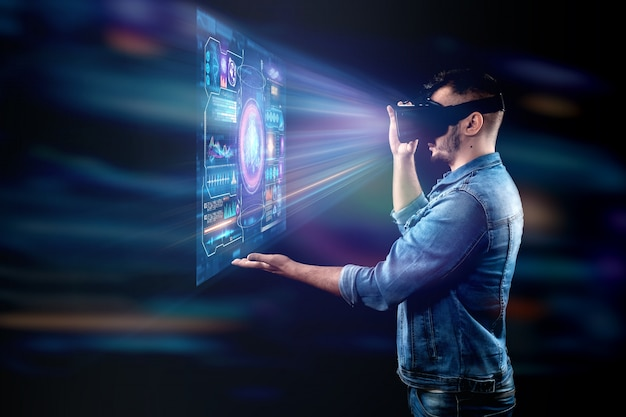 Portrait of a man with glasses of virtual reality, vr, interacts with a virtual screen Premium Photo