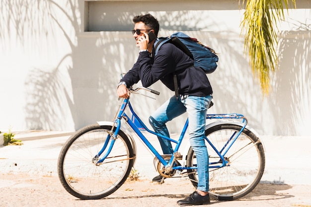 Portrait of a man with his backpack sitting on blue bicycle talking on smartphone Free Photo