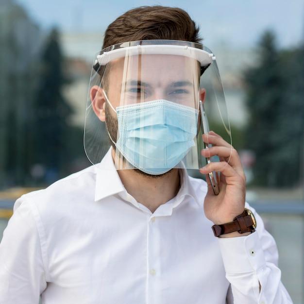 Uomo ritratto con maschera parlando al telefono Foto Gratuite