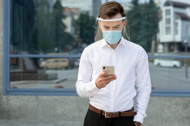 Ritratto di uomo con maschera utilizzando il cellulare Foto Gratuite