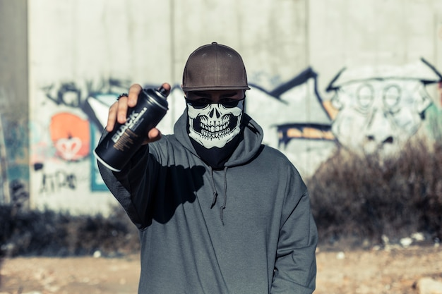 Portrait of a man with skull mask holding aerosol can Free Photo