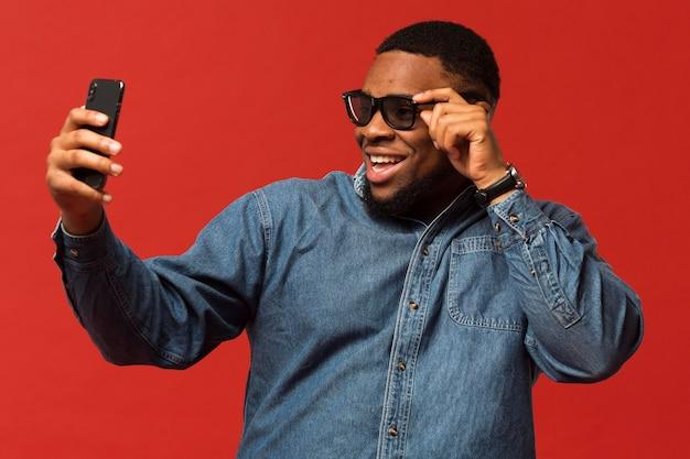Selfieを取ってサングラスを持つ肖像画男 無料写真