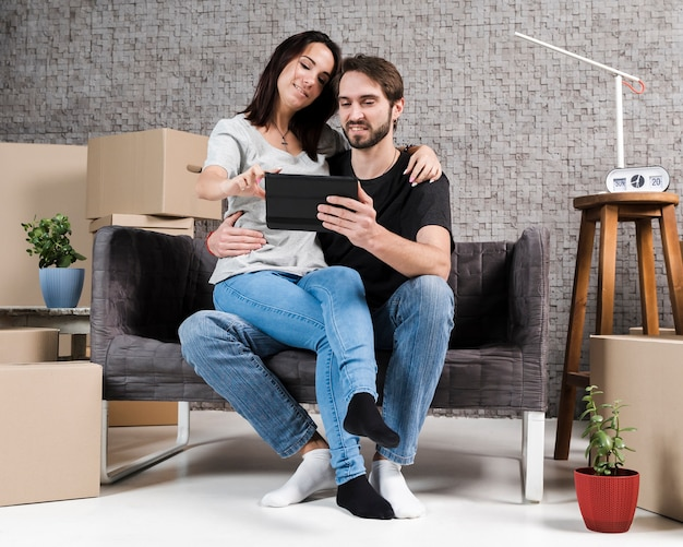Portrait of man and woman relaxing in new apartment Free Photo