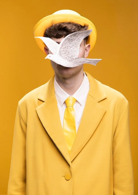 Portrait of man in yellow suit with silver pigeon in front of face Free Photo