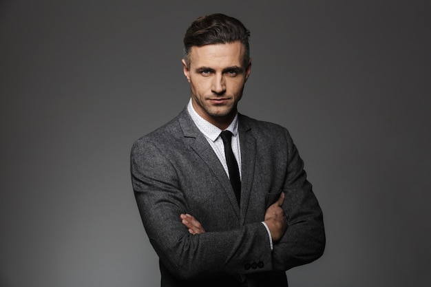 Portrait of masculine man wearing business suit posing  with serious look keeping arms folded, isol