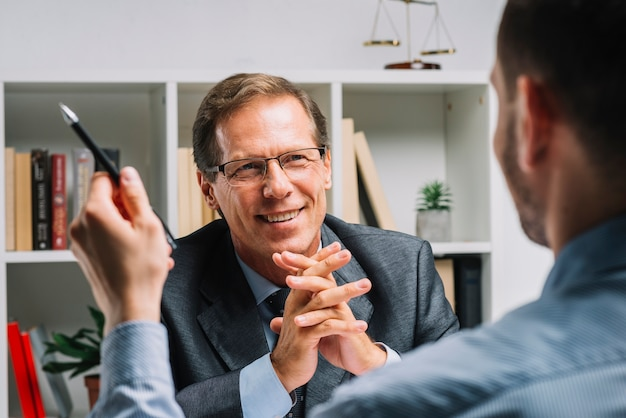 Portrait of mature happy lawyer sitting with client Free Photo