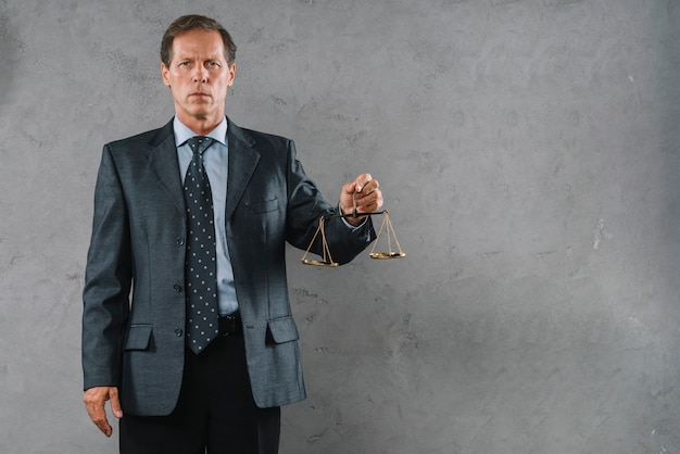 Portrait of mature male lawyer holding justice scale against gray textured background Premium Photo