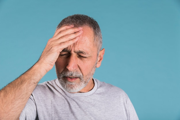 Portrait of a mature man suffering from headache Free Photo