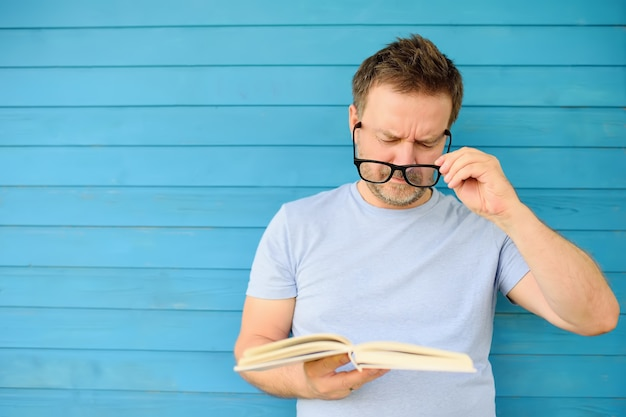 Portrait of mature man with big black eyeglasses trying to read book but having difficulties seeing text Premium Photo