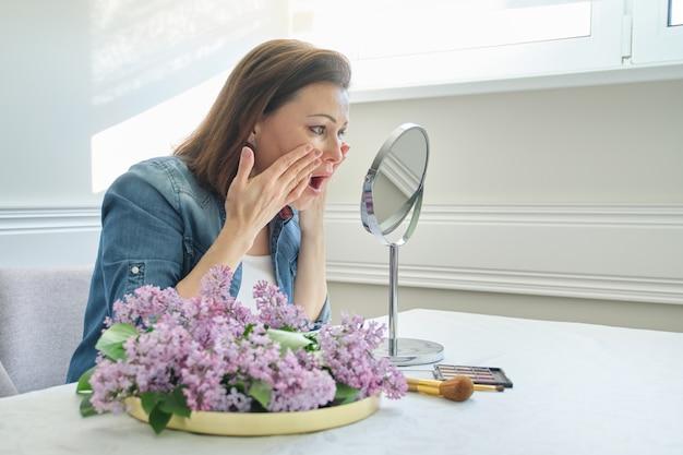 Portrait of mature woman with make-up mirror Premium Photo