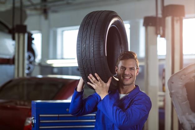 Ritratto di meccanico che trasporta un pneumatico Foto Gratuite