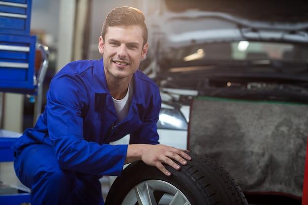 Ritratto di meccanico con un pneumatico Foto Gratuite