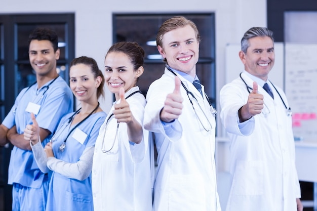 Portrait of medical team putting their thumbs up and smiling in hospital Premium Photo