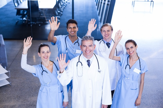 Portrait of medical team standing with their hand raised in hospital Premium Photo