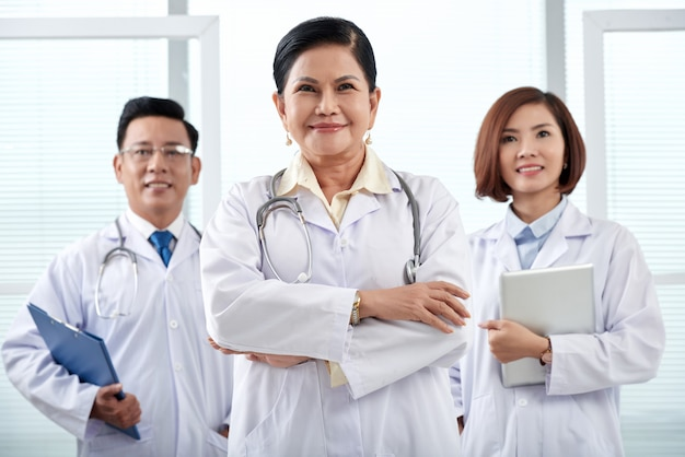 Portrait of medical team of three standing in the hospital looking at camera Free Photo