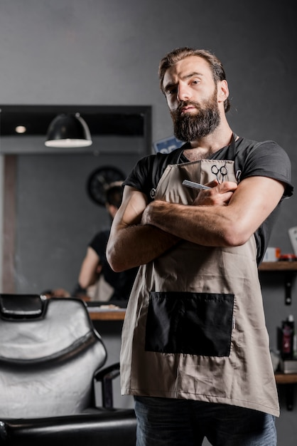 Portrait of a mid adult bearded male barber with folded arms Free Photo