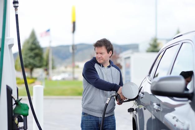 Portrait of middle age man filling gasoline fuel in car Premium Photo
