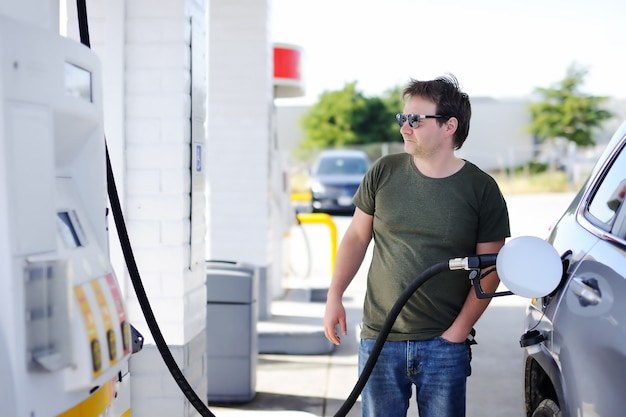 Portrait of middle age man filling gasoline fuel in car Premium Photo