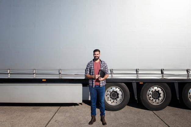 Ritratto di mezza età barbuto camionista in piedi davanti al rimorchio del camion contro il telone lucido grigio Foto Gratuite