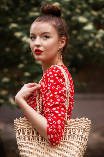 Portrait of a model large in a red dress and with a straw bag in the summer in the park after the rain Premium Photo