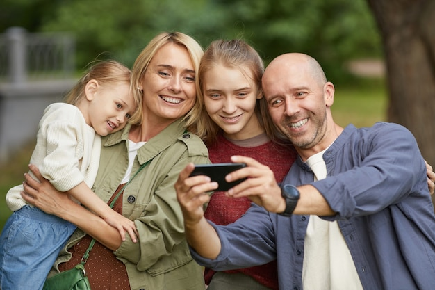 Portrait of modern happy family with two daughters taking selfie outdoors via smartphone while enjoying walk in green park Premium Photo