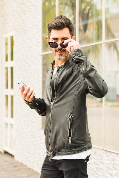 Portrait of modern man wearing black sunglasses holding smart phone in hand looking at camera Free Photo
