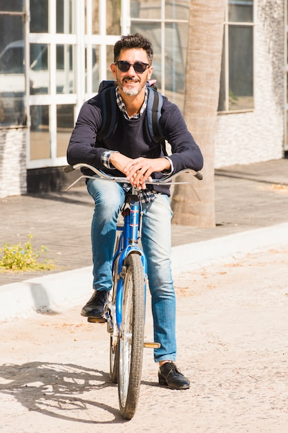 Portrait of modern man wearing black sunglasses sitting on bicycle Free Photo