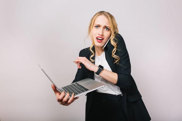 Ritratto di donna moderna bella bionda ufficio in camicia bianca e giacca nera, lavorando con il computer portatile, parlando al telefono. stupito, ritardo, turbamento, incontri, espressione di emozioni vere Foto Gratuite