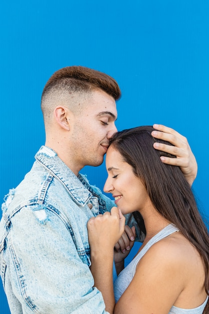 Portrait of a modern young man kissing a woman on the