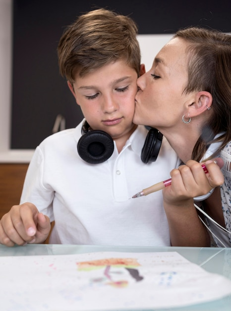 Portrait of mother kissing her son Free Photo