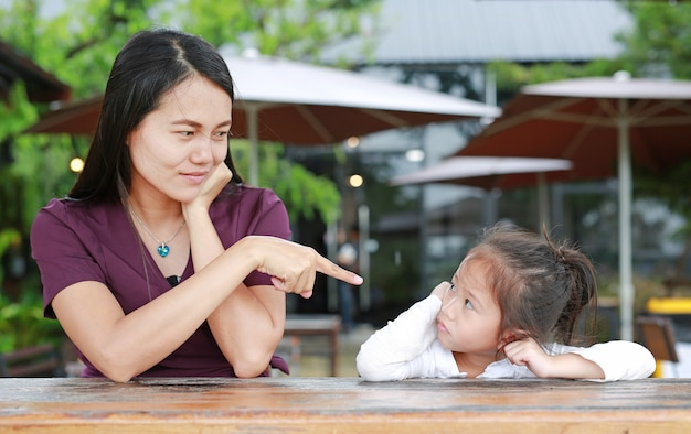 Portrait of a mother scolding to her daughter on the table. Premium Photo